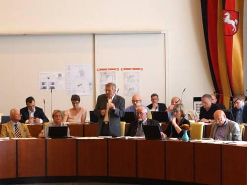 Mitglieder des Rates hören einem Redner im Sitzungssaal zu