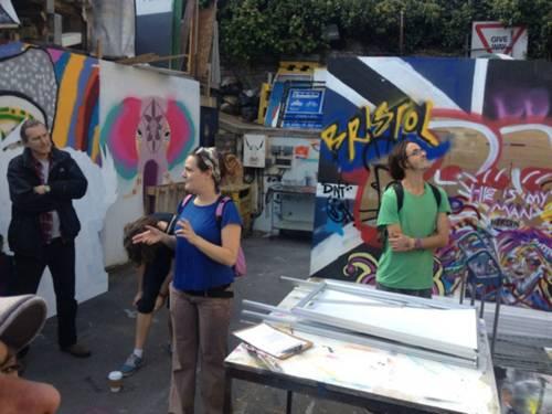 Eine Führerin erläutert den Zuhörenden das Gelände des Streetart Festivals. Im Hintergrund mit Graffiti besprühte Wände und Holzplatten.