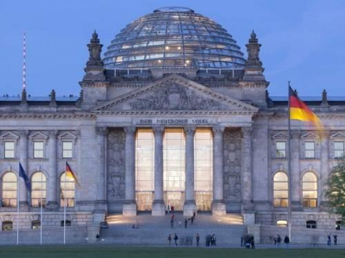 Blick vom Platz der Republik zum Westportal des Reichstagsgebäudes während der Dämmerung.