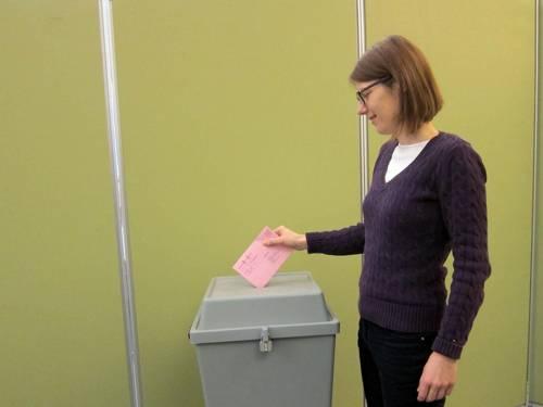 Eine Frau wirft einen Briefumschlag in eine Wahlurne (nachgestellte Szene)