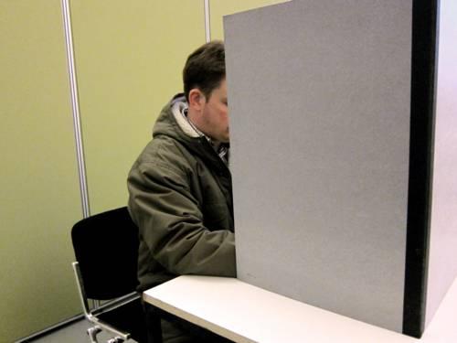 Nachgestellte Szene: Ein Wähler füllt seinen Stimmzettel in der Wahlkabine aus
