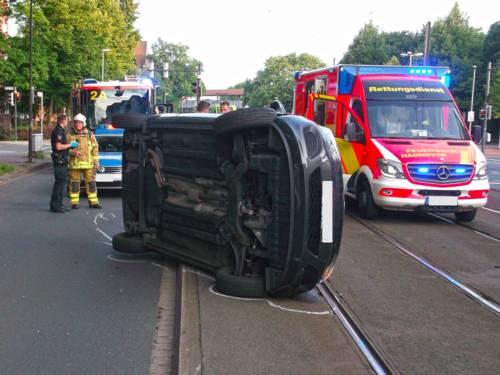Auf der Seite liegender PKW im Bereich der Stadtbahngleise. Dahinter ein RTW der Feuerwehr Hannover mit Einsatzkräften der Feuerwehr und der Polizei.