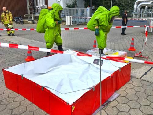 Zwei Einsatzkräfte in Chemikalienschutzanzügen. Im Hintergrund zwei weitere Einsatzkräfte der Feuerwehr Hannover.