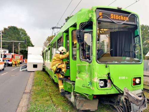 Im Vordergrund eine Einsatzkraft der Feuerwehr Hannover, die in die beschädigte Stadtbahn steigt. Im Hintergrund das beschädigte Führerhaus des LKWs sowie weitere Einsatzkräfte und Einsatzwagen.