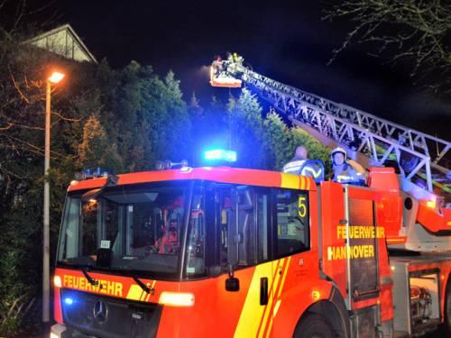 Mehrere Einsatzkräfte der Feuerwehr Hannover bei Löscharbeiten von einer Drehleiter.
