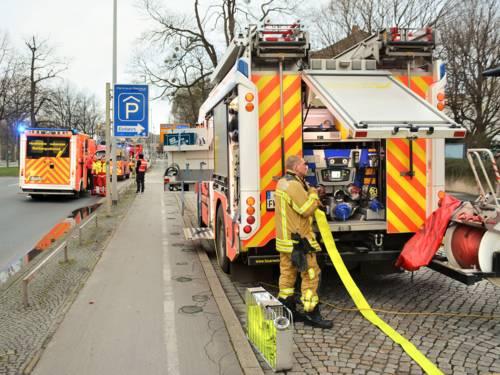 Mehrere Einsatzkräfte und Einsatzfahrzeuge der Feuerwehr Hannover vor der Flüchtlingsunterkunft am Friedrichswall.