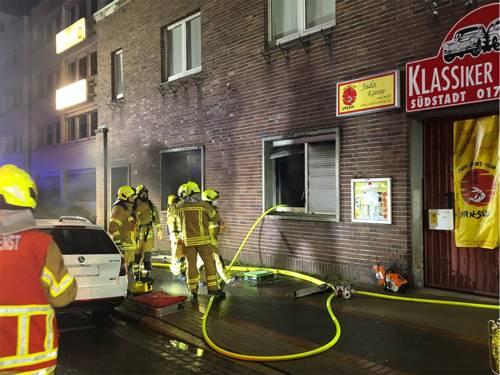 Feuerwehrleute vor einem verrauchten Fenster