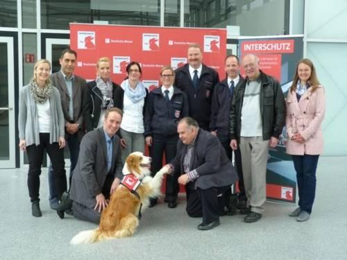 Die weltgrößte Messe für Brand- und Katastrophenschutz, Rettung und Sicherheit, die INTERSCHUTZ in Hannover, hat jetzt ein eigenes Maskottchen: Rettungshund Timmy. Messe-Projektleiter Heinold und das Team von Deutscher Messe AG, vfdb und Feuerwehr Hannover begrüßen Timmy.