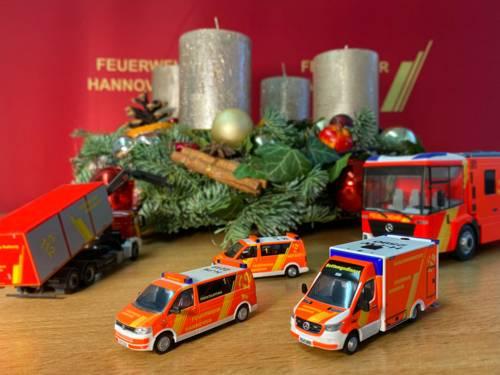 Ein Adventskranz und Miniaturautos der Feuerwehr