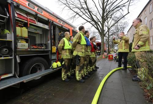 Auszubildende Feuerwehrmänner stehen vor einem Fahrzeug