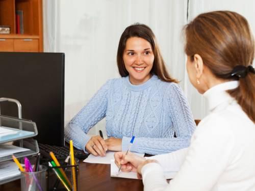 Zwei Frauen an einem Schreibtisch im Gespräch