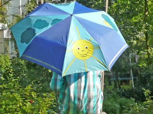 Ein Kind versteckt sich hinter einem Regenschirm, der mit einer lachenden Sonne, aber auch mit dunklen Wolken bedruckt ist.