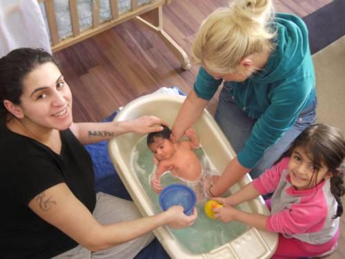 Ein neugeborenes Baby wird in einer kleinen Wanne liebevoll gebadet