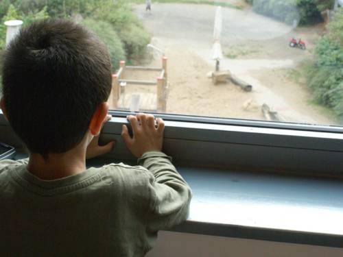Ein Junge steht am Fenster