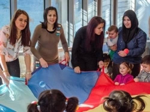 Eltern und Kita-MitarbeiterInnen mit Kindern an einem Schwungtuch