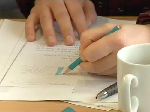 Eine schreibende Hand, im Vordergrund eine weiße Kaffeetasse