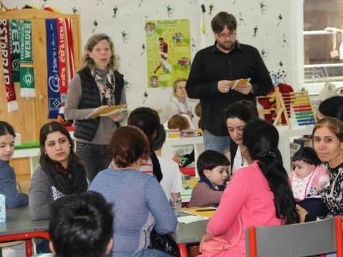 An mehreren Tischen sitzen Kinder und Erwachsene, während eine Moderatorin und ein Moderator im Stehen mit den Anwesenden sprechen.