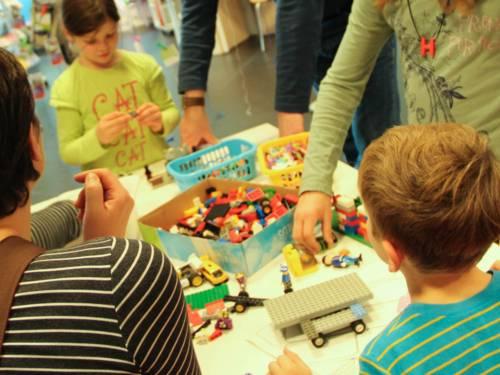 Kinder an einem Tisch basteln im Beisein von Erwachsenen mit Legosteinen