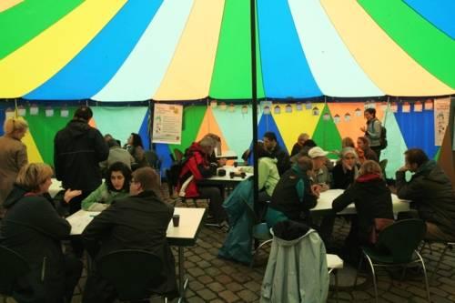 BürgerInnen diskutieren in einem bunten Rundzelt an verschiedenen Tischen miteinander und notieren ihre Ideen auf Papiertischdecken