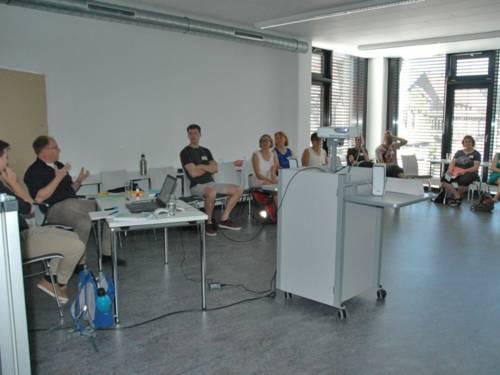 Vortragende und Zuhörer in einem Raum