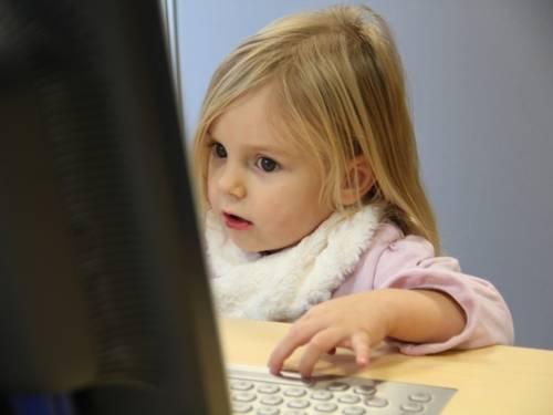 Ein kleines Mädchen sitzt an einem Computer-Arbeitsplatz