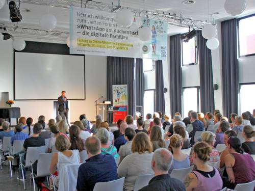Moderator Tim Gailus auf der Bühne, davor vollbesetzte Sitzreihen mit vielen Zuhörerinnen und Zuhörern