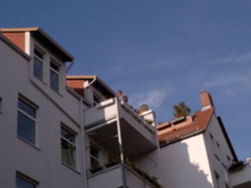 Weißes Wohnhaus. Auf dem obersten Balkon steht ein Mann mit einem Baby auf dem Arm.