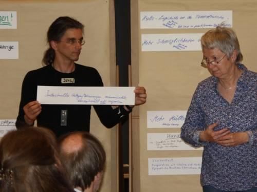 Ein Mann und eine Frau präsentieren Diskussionsergebnisse auf Papierstreifen an einer Pinnwand.