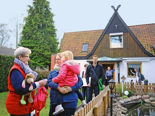 Familie mit drei Generationen vor einem Einfamilienhaus mit Garten