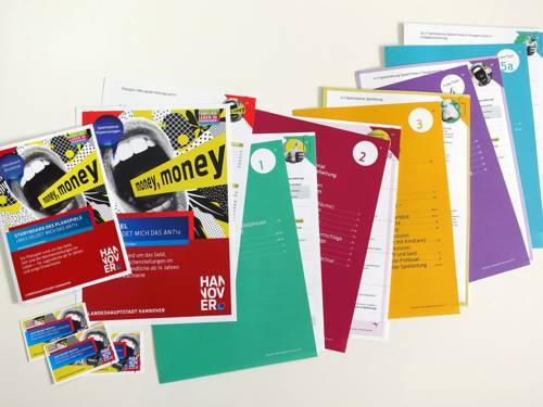 Mehrere bunte Broschüren und Flyer liegen aufgefächert auf einer hellen Fläche.