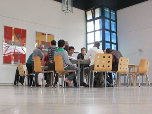 Ein Gruppe junger Männer beim Deutschunterricht im ehem. Oststadtkrankenhaus