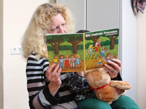 Eine Frau liest einem Kind aus einem Buch vor