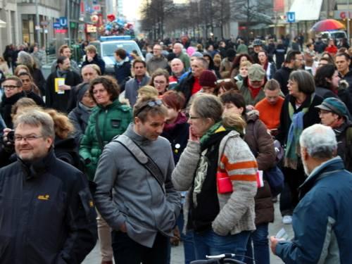 Blick von der Bühne neben der Uhr am Kroepcke in Richtung Steintor: Etwa 100 sichtbare Teilnehmer/innen blicken zur Bühne in Richtung Opernplatz.