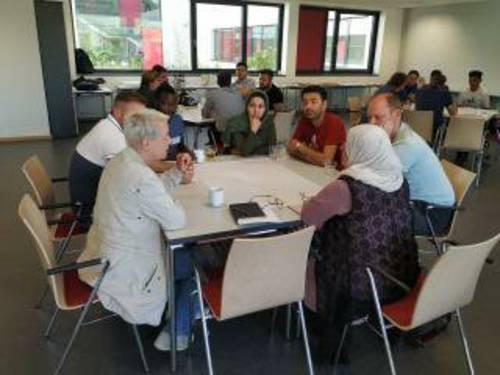 Sieben Personen - zwei Frauen und fünf Männer - sitzen kreisförmig an zusammengeschobenen Tischen und diskutieren miteinander.