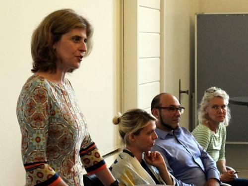 Vier Personen - drei Frauen und ein Mann - sitzen nebeneinander an Tischen im Gobelinsaal des Neuen Rathauses. Die Frau links im Bild steht und spricht.