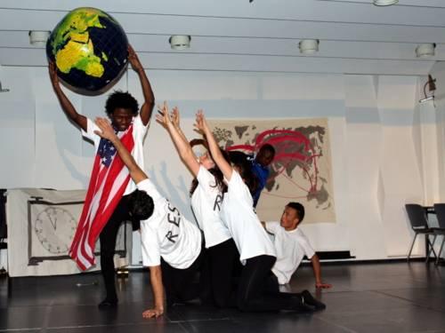 Ein Darsteller hält eine große Weltkugel hoch und trägt eine USA-Flagge um den Schultern. Dahinter steht ein weiterer Darsteller mit der EU-Flagge. Vier weitere Darsteller/innen sitzen auf dem Boden und strecken die Hände nach dem Erdball aus.