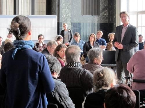 Rechts im Bild steht ein Mann zwischen den sitzenden Teilnehmer/innen und blickt zu einer ebenfalls stehenden Frau links im Bild, die spricht.