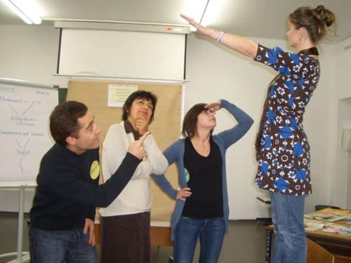Rollenspielsituation: In einem Unterrichtsraum blicken ein Mann und ein Frau zu einer Frau auf, die mit ausgestrecktem Arm auf einem Stuhl steht, während eine dritte Frau nachdenklich wegschaut.