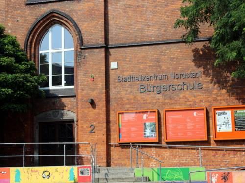 """Backsteingebäude am Sprengel-Gelände. Rechts vom Eingang steht ein Schriftzug, auf dem steht: """"Stadtteilzentrum Nordstadt Bürgerschule"""""""