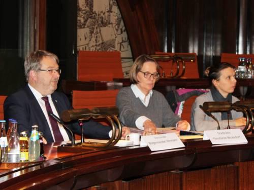 Drei Personen - zwei Frauen und ein Mann - sitzen im Hodlersaal nebeneinander hinter Pulten