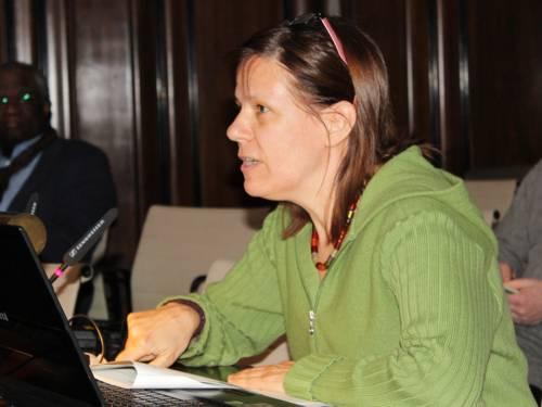 Eine Frau sitzt im Hodlersaal an einem Pult, auf dem ein aufgeklappter Laptop steht.