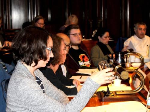 Sechs Personen sitzen im Hodlersaal des Neuen Rathauses an Pulten. Einige davon blicken nach vorne, andere auf Unterlagen, die vor ihnen liegen.