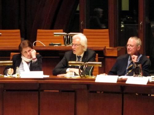 Im Hodlersaal sitzen drei Personen in einer Reihe. Die Linke stützt den Kopf ab und bickt nach rechts, die Mittlere redet, die Rechte schaut leicht nach links. Vor den Personen stehen Namensschilder und eine Tischlampe mit zwei fest verbauten Mikrofonen.