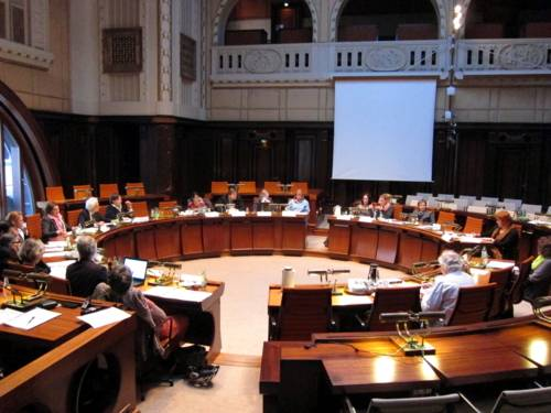 Die Ausschussmitglieder sitzen kreisförmig hinter Pulten im Hodlersaal. Einige Plätze sind unbesetzt.