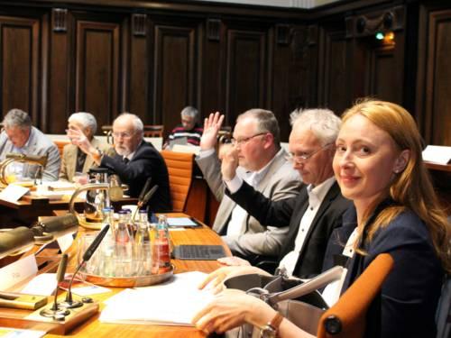 Sechs Personen sitzen nebeneinander an Pulten im Hodlersaal. Drei davon heben die Hand zur Abstimmung.