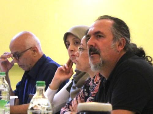 Drei Personen - zwei Männer und eine Frau - sitzen nebeneinander an Tischen, auf denen Getränke und Papierunterlagen liegen.