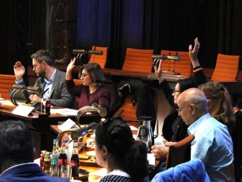 Sieben Personen - vier Frauen und drei Männer - sitzen im Hodlersaal des Neuen Rathauses hinter Pulten. Vier davon heben die Hand zur Abstimmung.