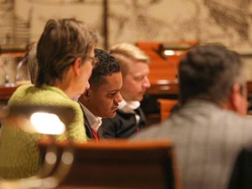 Vier Personen sitzen im Hodlersaal des neuen Rathauses hinter Pulten.