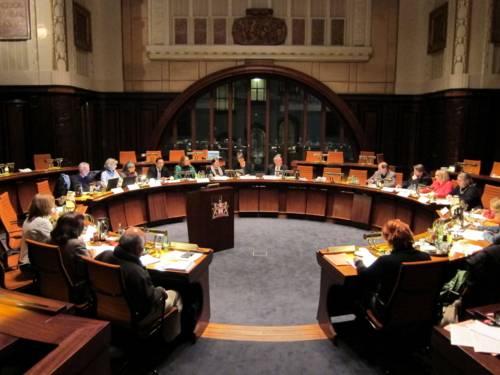 Etwa 20 Personen sitzen kreisförmig hinter Pulten im Hodlersaal.