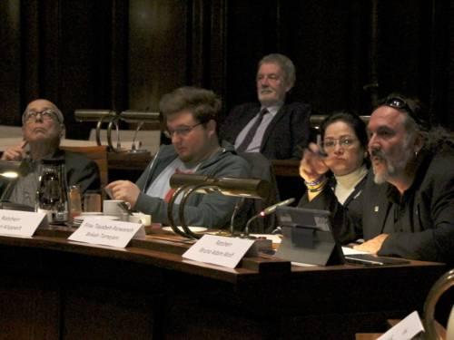 Vier Personen sitzen nebeneinander im Hodersaal des Neuen Rathause. Ein Mann ganz rechts sitzend spricht.
